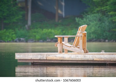 Adirondack chairs sitting on a wooden dock facing a calm lake.