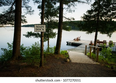 Adirondack chairs sitting on a wooden dock at sunrise. Hanging on a tree there's a sign indicating the main dock