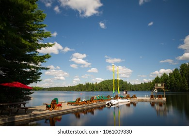 Adirondack and lounge chairs sitting on a wood dock facing a calm lake during a sunny day. Sailing boats are tied to the dock.