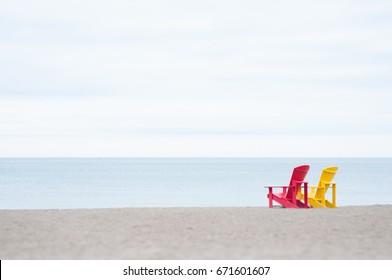 Adirondack or Muskoka Chairs  on a lake shore, summer day, holiday, beach