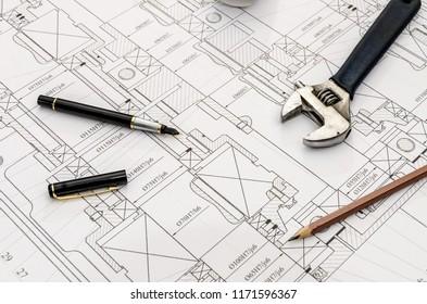 Adjustable key, pen and pencil on blueprint background
