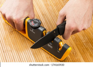 adjustable manual knife sharpener on wooden background