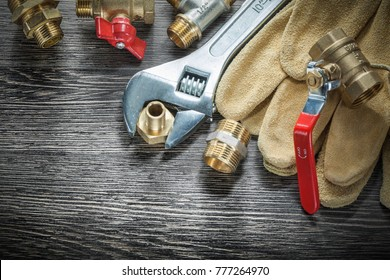 Adjustable spanner water valve pipe fittings leather safety gloves on wooden board.