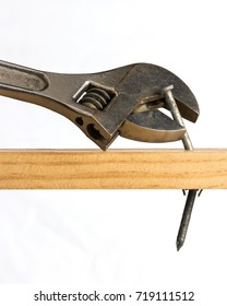 An adjustable wrench is shown attempting to be used to pry a nail from a piece of wood
