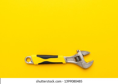 adjustable wrench with yellow handle on the yellow background. minimalist photo of adjustable wrench with copy space