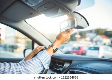 Adjusting the rear view mirror. Hand adjusting rear view mirror. Safety concept. Woman adjusting rear view mirror.