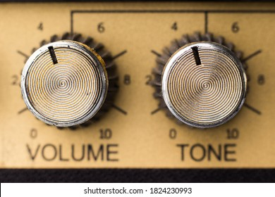 Adjustment knobs in the panel of an electric guitar amplifier, close up with selective focus