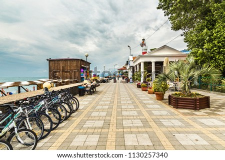 Adler, Russia - June 17, 2015: Adler embankment with resting people on a cloudy day, Russia