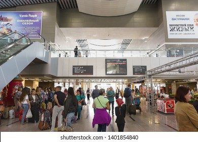Adler, Sochi, Russia - may 05, 2019: Many passengers waiting for the arrival of the desired train at the passenger railway station. Information boards and advertising banners on the walls