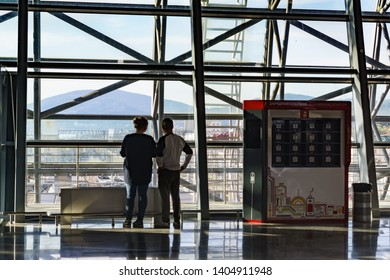 "Adler, Sochi, Russia - may 05, 2019: Passengers at the window in the waiting room of a large modern railway station. Installation for charging mobile phones and tablets ""Charging station"""