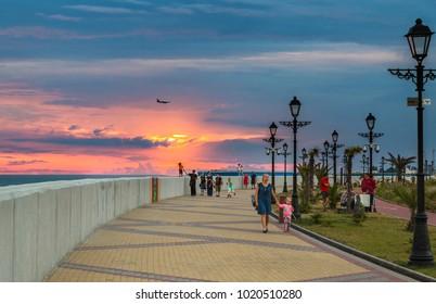 Adlersky, Russia - June 17, 2015: People walking at sunset on the promenade of Adler, Sochi