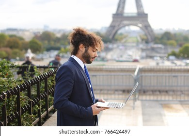 administrator of tourist company working on open air with modern laptop near Eiffel Tower in slow motion. Handsome man dressed in black suit, white shirt and blue tie, has dark fleecy hair and