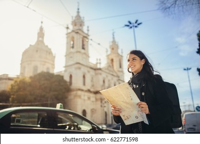 Admiring amazig sunset in european metropola.Traveling in Europe.Female turist in front of Basilica da Estrella and famous 28 tram in Lisbon,Portugal.Woman holding maps and exploring charming country