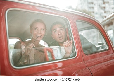 Admiring the city. Amazed tourists looking out of the windows of red retro-car, woman smiling and biting her eyeglasses and man opening his mouth.