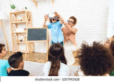Admiring little boy stands in virtual reality glasses in primary school classroom. Children's acquaintance of with high technologies.