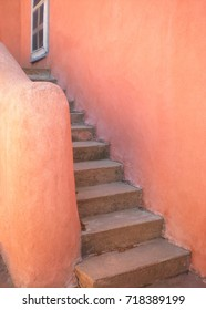 Adobe architecture exterior with stairway and thick orange clay walls.