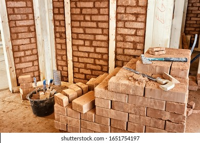 Adobe bricks filling the compartments of the framework of an eco