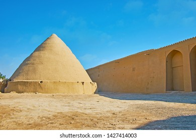 Adobe construction of yakhchal (ice chamber) - ancient evaporative cooler, shaped as spiral pyramid, located next to the rampart of Ghal'eh Jalali fortress, Kashan, Iran