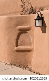 Adobe earthen wall exterior fascade with decorative wall recession and glass lantern.