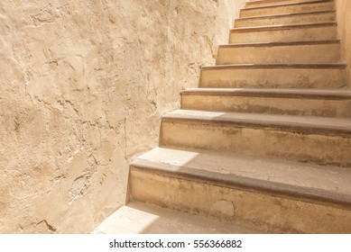 An adobe flight of stairs against a plaster wall of the courtyard of a traditional Arabian house.