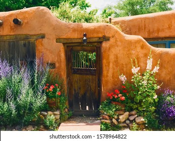 Adobe wall with wooden door and flower garden
