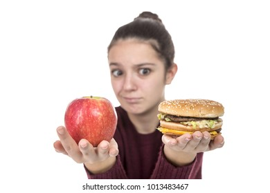 Adolescent girl choosing between fruit and a hamburger on a white background