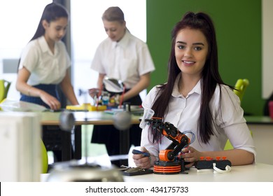 Adolescent girl in a design and technology lesson. She is smiling at the camera with a robotic arm that she is building infront of her.