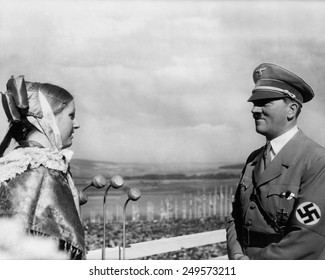 Adolf Hitler with a young woman in folk costume at the 1935 Erntedankfest. The Erntedankfest was an important component of Nazi, 'blood-and-soil ideology'.