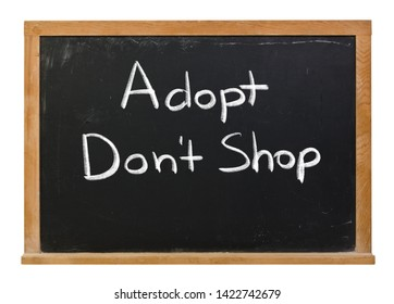 Adopt don't shop written in white chalk on a black chalkboard isolated on white