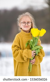 Adorabe little girl wearing adult oversized sweater and big fathers boots. Beautiful young  girl in glasses standing on bench with bouquet of yellow tulips in snowy winter day.