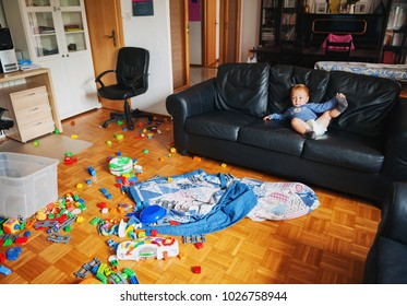 Adorable 1 year old baby boy with funny facial expression playing in a very messy living room, lying on a couch, watching tv