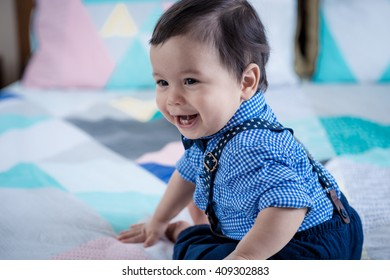 Adorable 11 month old mixed race Asian Caucasian boy dressed in braces and a bow tie plays cheerfully on a colorful geometrically shaped bed cover. Natural indoor lighting