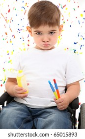 Adorable 2 year old boy in wheelchair holding paint and brushes on paint splattered background.