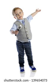 An adorable 2-year-old boy giving his grand finale with a microphone in one hand and his other extended.  On a white background.