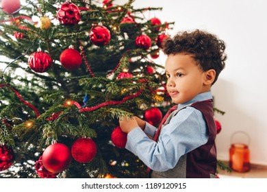 Adorable 3 year old toddler boy decorating Christmas tree