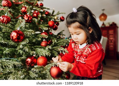 Adorable 3 year old toddler girl decorating Christmas tree, wearing red pullover