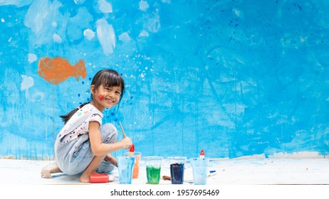Adorable 5 years old asian little girl is smiling while painting the wall with water color at home, concept of art education for kid, homeschooling and learning activity by playing for child.