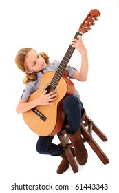 Adorable 7 year old blond girl playing acoustic guitar over white background.