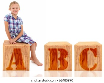 Adorable 7 year old blond american girl sitting on wooden box over white background. Letters ABC.