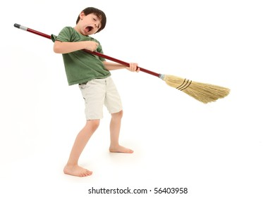 Adorable 7 year old boy child doing chores and playing air guitar with broom.