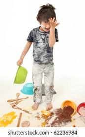 Adorable 7 year old boy making mess baking cookies.