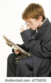 Adorable 7 year old boy in baggy suit and glasses reading newspaper.