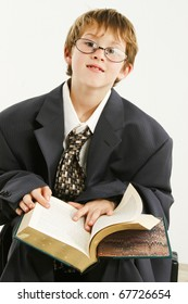 Adorable 7 year old boy in baggy suit and glasses reading book.