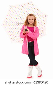 Adorable 7 year old girl in rain gear and pokadot umbrealla over white background.
