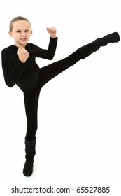 Adorable 7 year old girl in black demonstrating a martial arts kick over white background.
