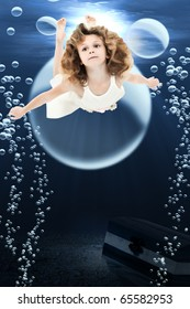 Adorable 7 year old girl in dress swimming under ocean swimming past treasure chest and bubbles.