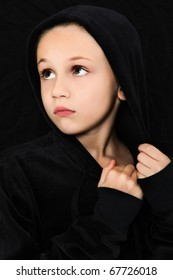 Adorable 7 year old girl in black looking to side with worried or scared expression.