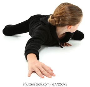 Adorable 7 year old girl in black suit crawling and looking behind on white floor.