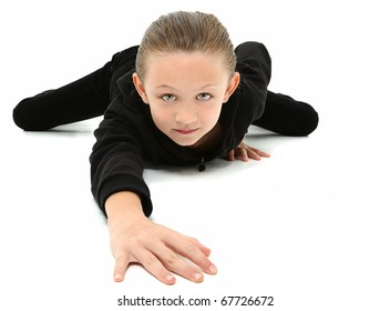 Adorable 7 year old girl in black suit crawling on white floor.