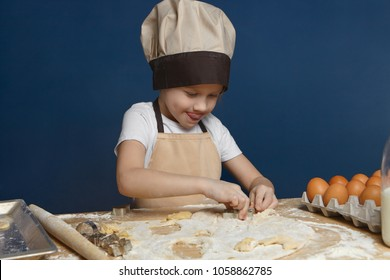 Adorable 8 year old male child in beige apron and hat standing in kitchen, molding cookies on counter, trying hard, sticking out tongue. Focused little boy making pasty at table covered with flour